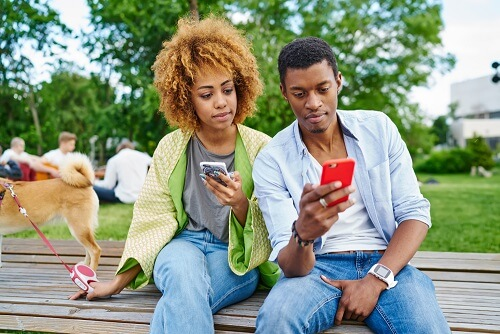 young couple sitting in the park and using their cellphones