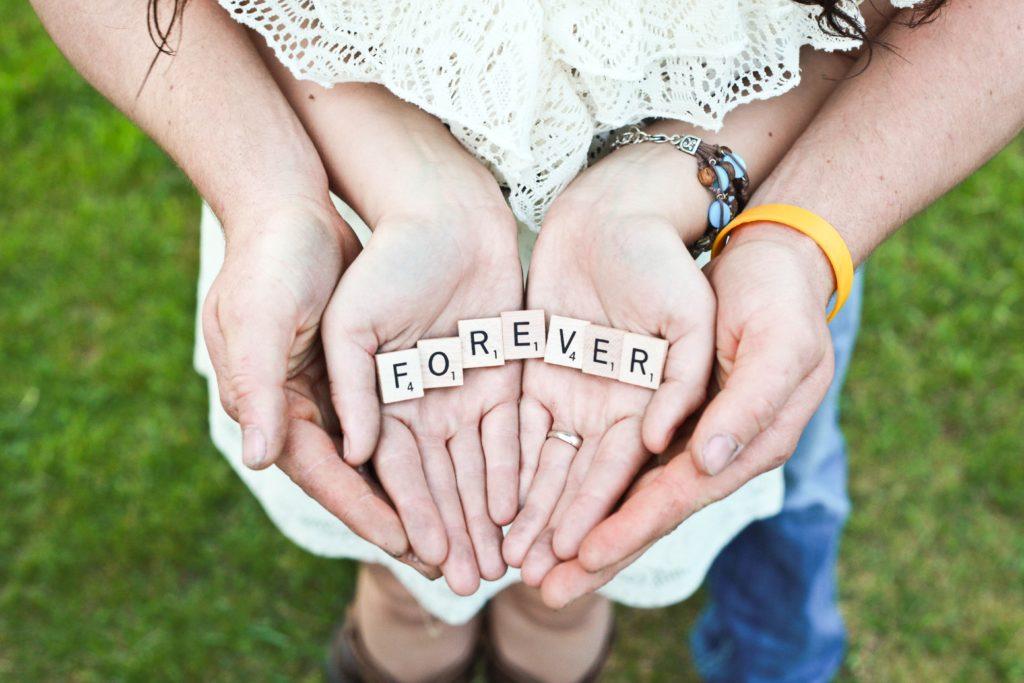 """Paar, das sich an den Händen hält und mit Scrabble-Stücken das Wort """"für immer"""" bildet."""