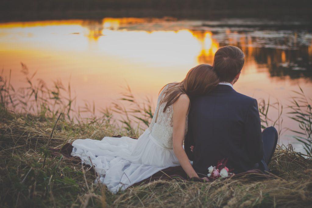 christliches Paar, das romantisch an einem See sitzt