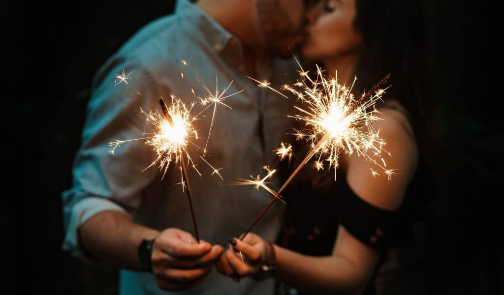 couple with fireworks on their hands kiss each other