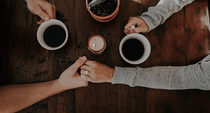 couple holding hands over coffee
