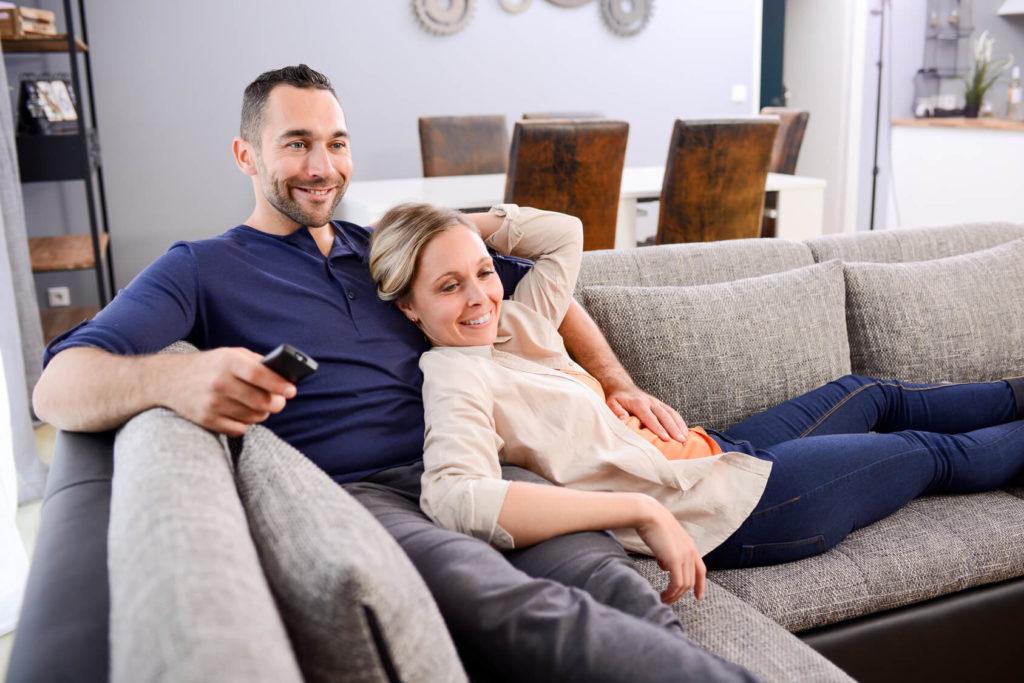 Ehepaar mit Altersunterschied sieht im Wohnzimmer gemeinsam fern