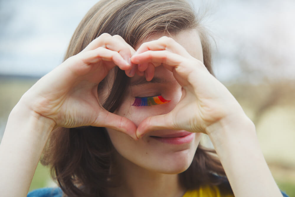 A sweet short hair girl wearing rainbow mascara doing a heart gesture