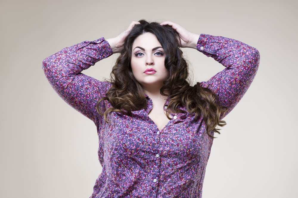 Charming curvy woman in purple shirt putting her arms on the head