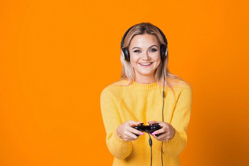 attraktives blondes Gamergirl, das vor orangem Hintergrund lacht und posiert