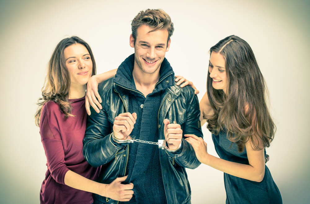 Two good looking women with a hot guy handcuffed. Three of them are all smiling.