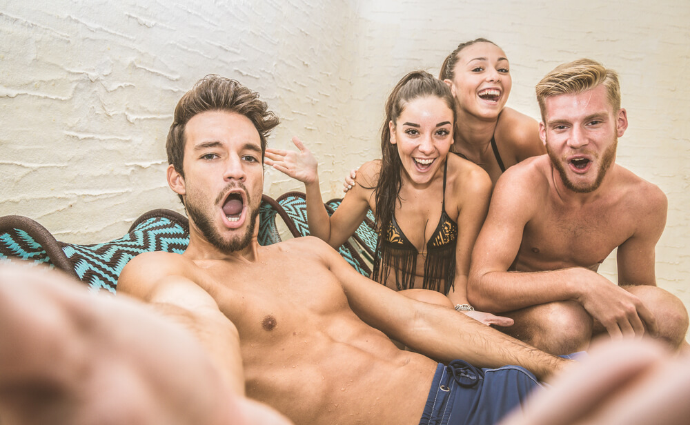 Two hot couples taking a selfie together. Women are in the bikinis, and men are topless