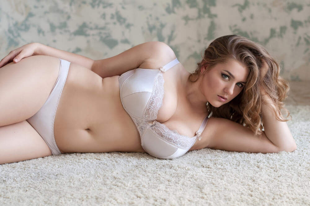 Sexy curvy woman lying on the carpet with her bra and underwear on, staring into the camera.