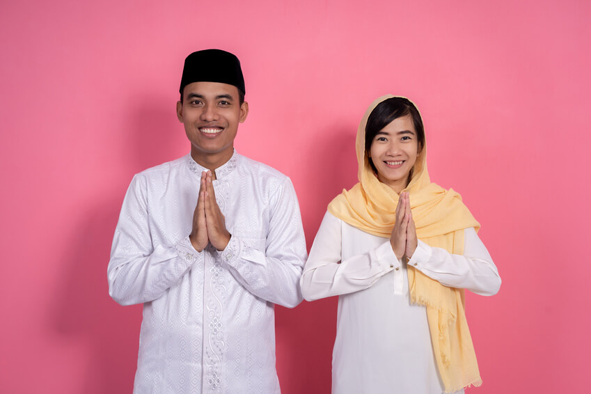 conservative muslim couple smiling into camera