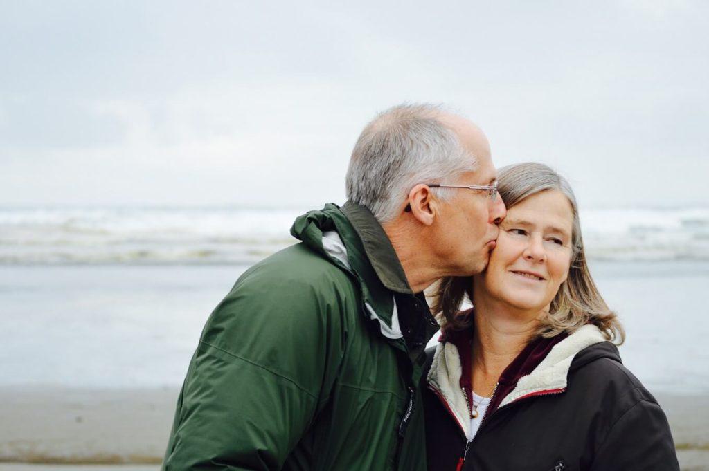 altes Paar über 50 Jahre, das sich am Strand trifft und sich auf das Gesicht küsst