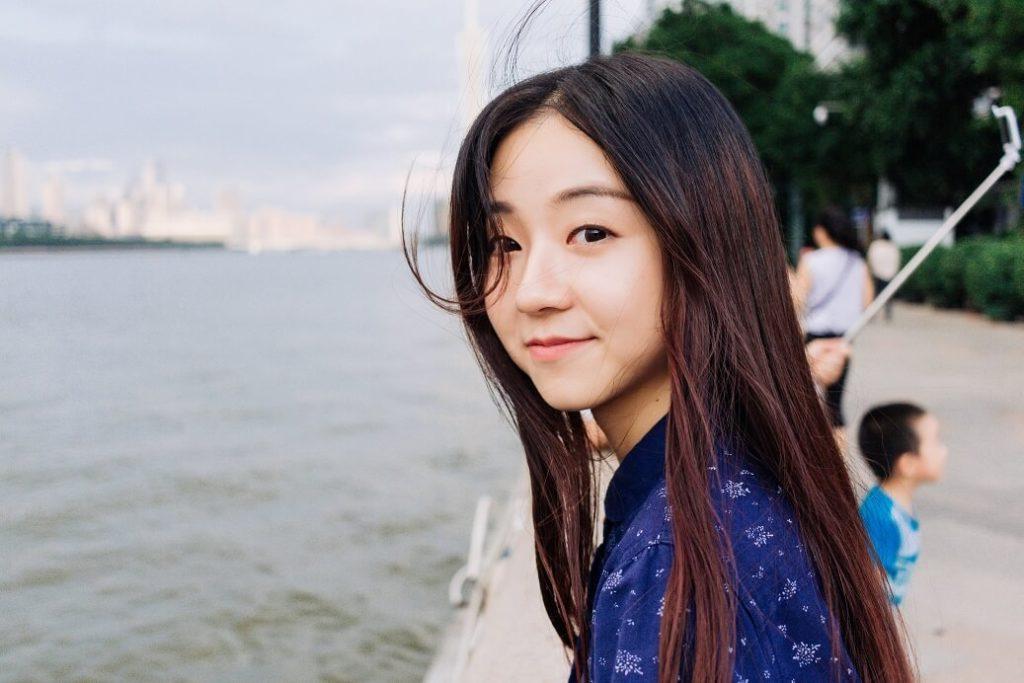 hübsches asiatisches Mädchen, das in einer Bucht in die Kamera schaut