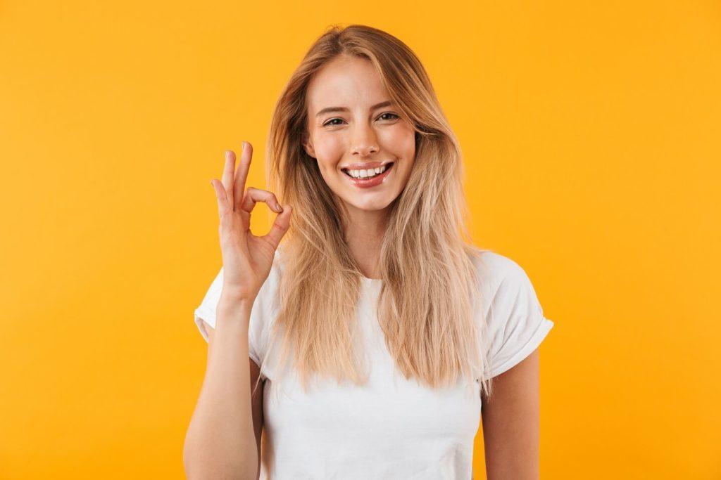 sehr attraktives taubes Mädchen, das in die Kamera lächelt und ein Handzeichen macht