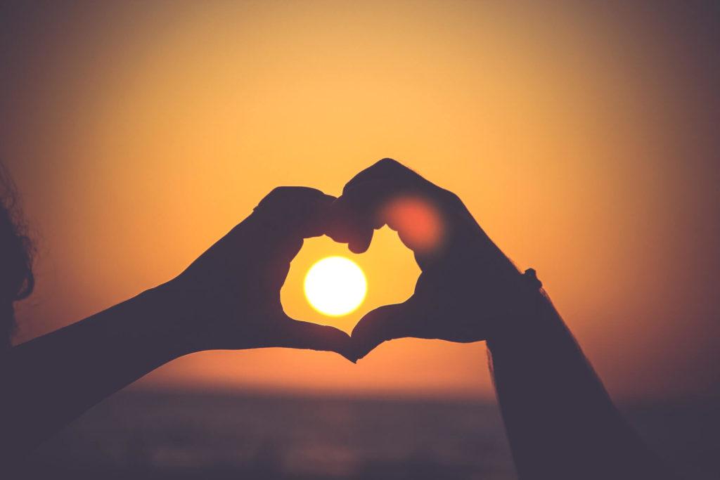 Ein Paar, das mit den Händen ein Herz bildet, während die Sonne untergeht