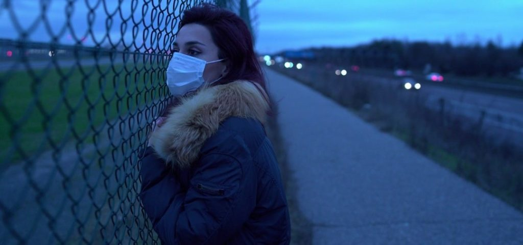 Woman at a fence with mask