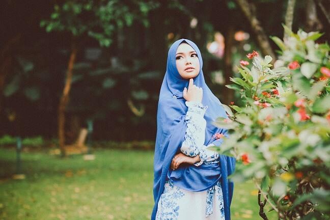 attractive muslim girl standing in a garden