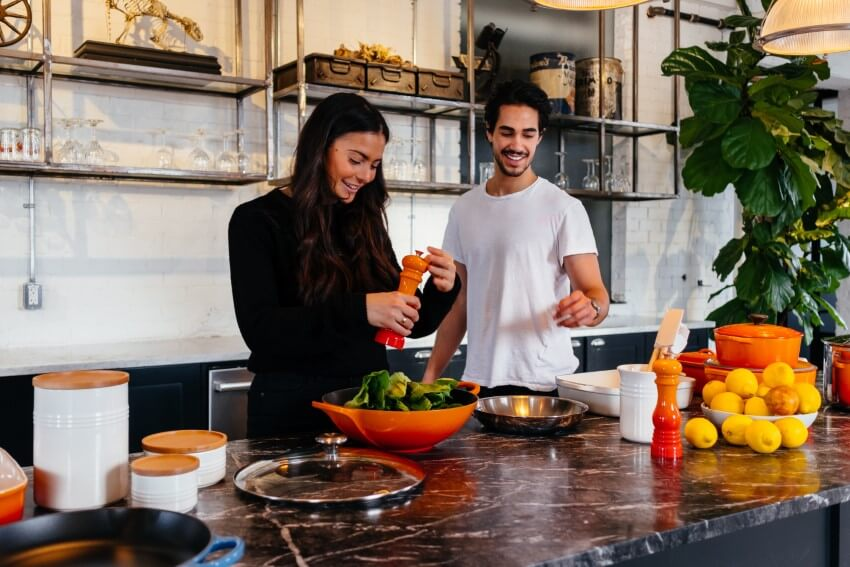 happy couple preparing a salad in their kitchen while dating vegan
