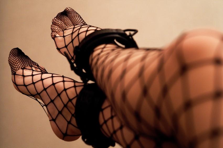 BDSM sub legs in fishnet