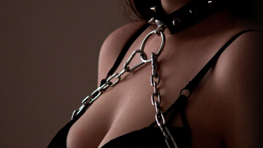 BDSM woman in chains and choker
