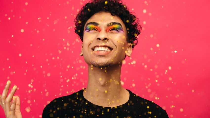 trans guy with colorful pride make-up throwing golden confetti