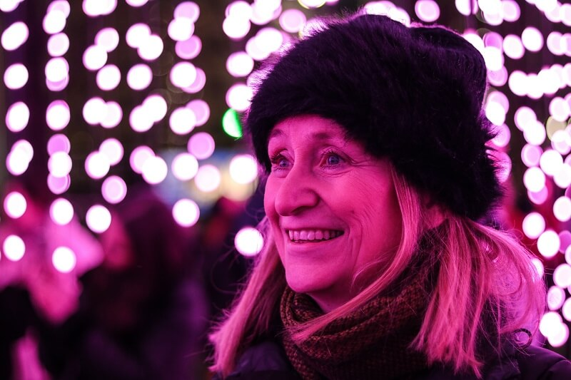 Granny is excited and smiling at a christmas fair