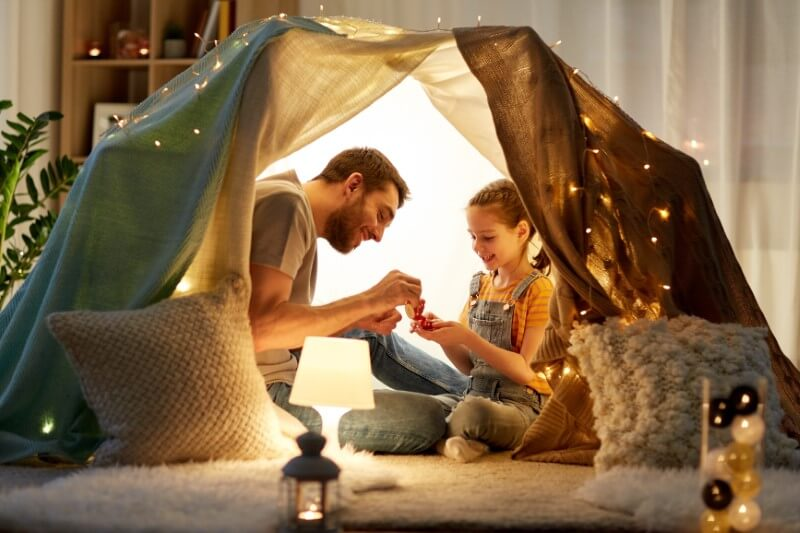 single dad has built an indoor tent with his daughter and they're having a tea party