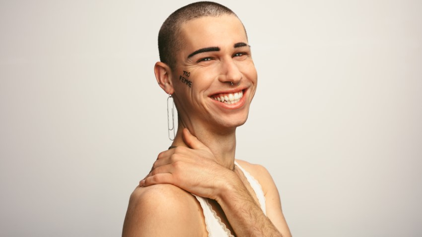 smiling non-binary trans person with writing on the cheek that says 'too femme'