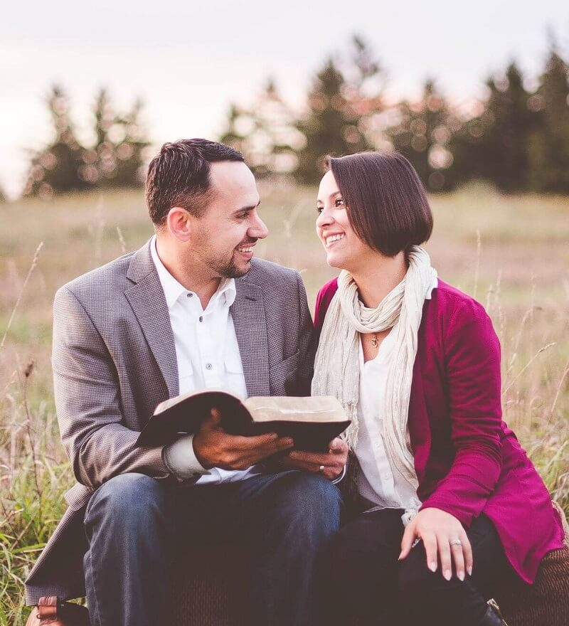 Happy Christian couple sitting in a field with a Bible