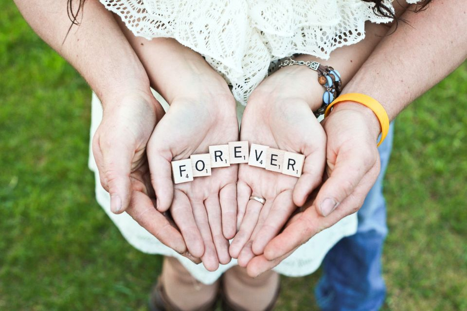 Couple standing with hands together and Scrabble pieces spelling 'Forever' in woman's hands