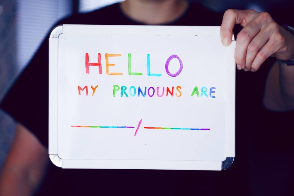 """someone holding up board that says """"hello my pronouns are none"""""""