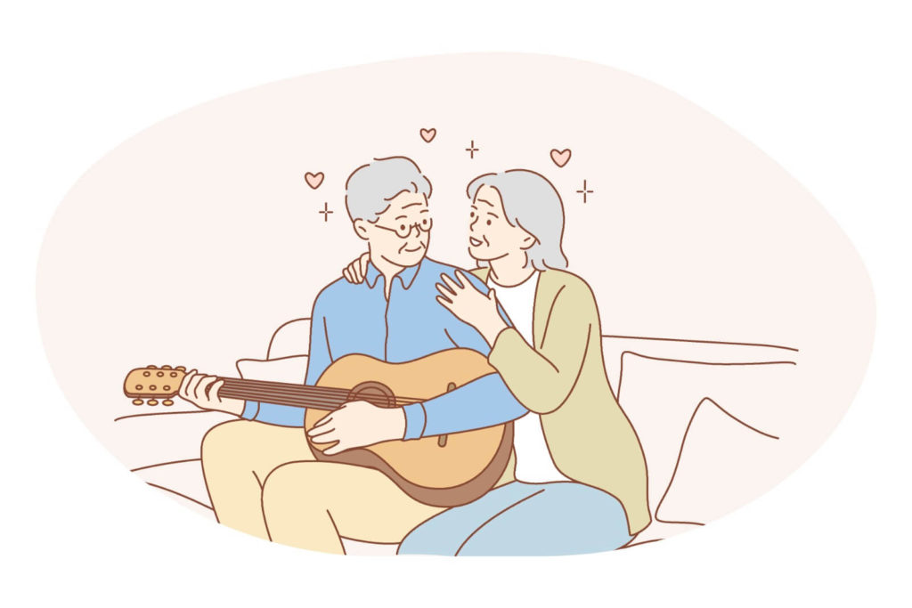 old couple sitting down on a sofa while she hugs him from behind as he plays the guitar
