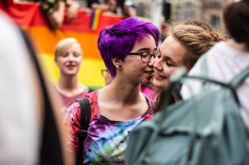 two young girls about to kiss at a pride march