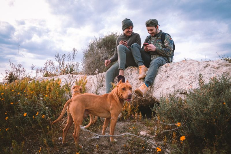 two guys and a dog hanging out in nature