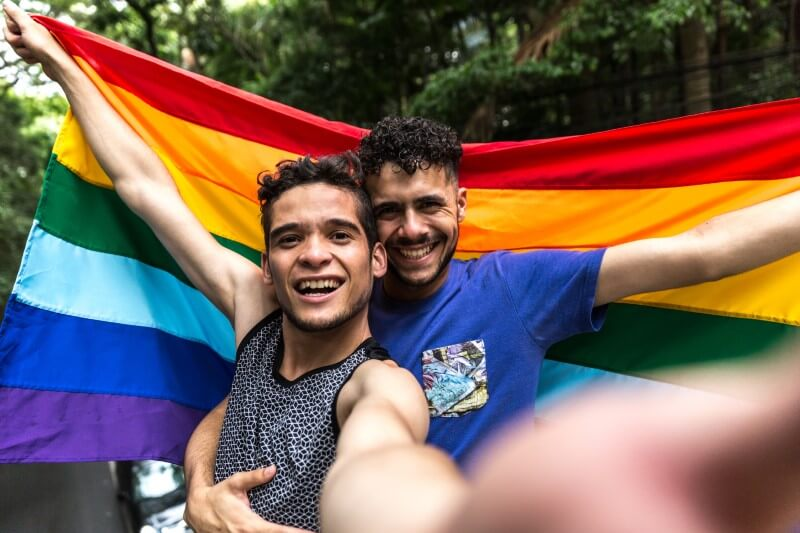 selfie of two men with a gay pride flag
