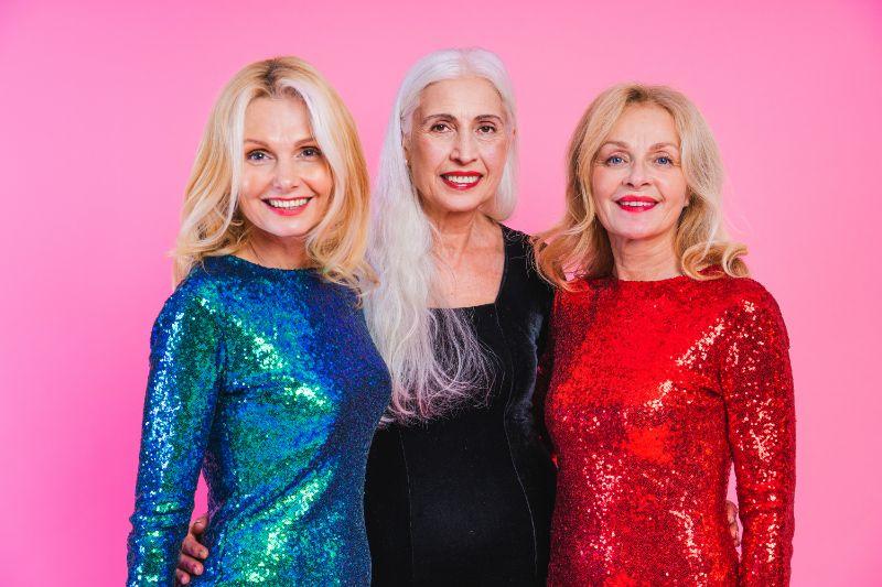 three elegant older women in fancy dresses